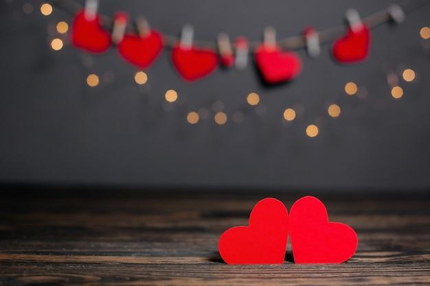 Пара красных сердец на фоне огней, любви и валентинки на деревянном столе