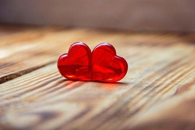 빈티지 나무 테이블 상단보기에 빨간 하트의 쌍. 세인트 발렌타인 데이 인사말 카드입니다.