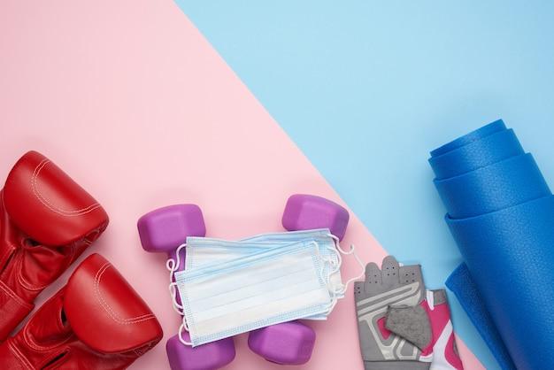 Пара красных кожаных боксерских перчаток, синий неопреновый коврик.