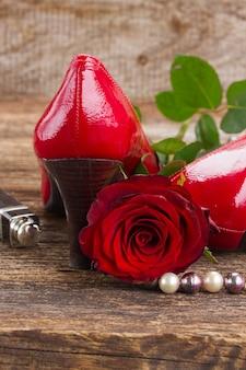 木製の背景にバラの花と赤い靴のペア