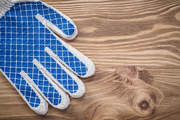 Пара защитных рабочих перчаток на деревянной доске