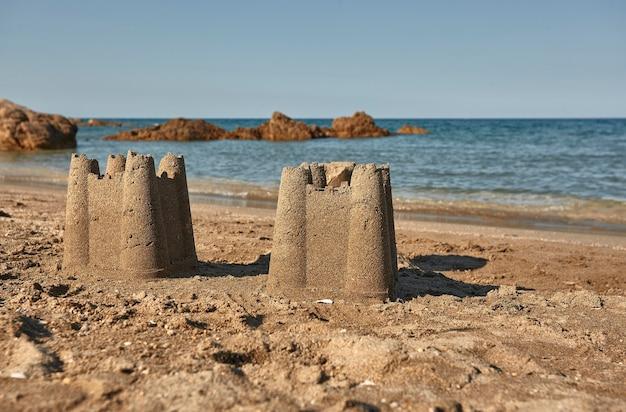 사르데냐 남부 칼라 사 피구(cala sa figu) 해변의 황금빛 모래 위에 지어진 한 쌍의 모래 성