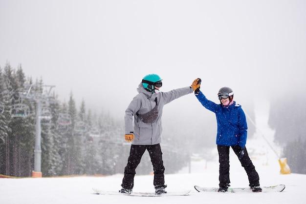 スキー場でリフトを使ってハイタッチするスノーボーダーのペア。背景に降る雪の中の濃霧の景色