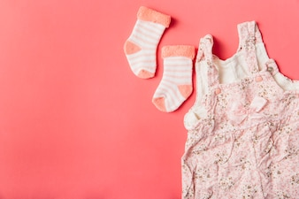 Pair of sock and baby dress on bright colored background