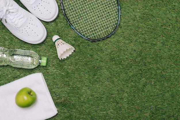 Пара спортивной обуви, свежее яблоко и аксессуары для спорта на зеленой траве, здоровый и активный образ жизни, место для текста или надписи