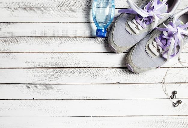 흰색 나무 배경에 스포츠 신발, 물병 및 이어폰의 쌍