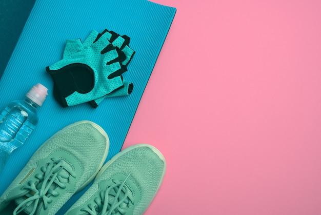 Пара спортивных кроссовок и бутылка с минеральной водой на розовом фоне, вид сверху, копия пространства