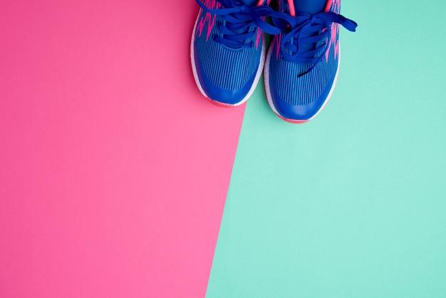 色付きの抽象的な背景に青いひもでスポーツスニーカーのペア