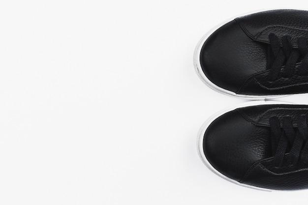 白い背景の上のスタイリッシュな黒のスニーカーのペア