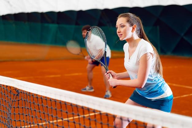 Пара теннисистов, мужчина и женщина в ожидании службы на крытом корте