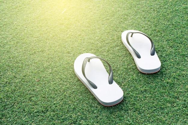 バースト日の出光、夢のソフトスタイルと緑の草の背景の白いビーチサンダルのペア