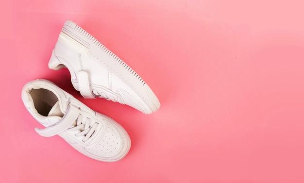 Пара белых кожаных кроссовок, изолированных на розовом фоне.