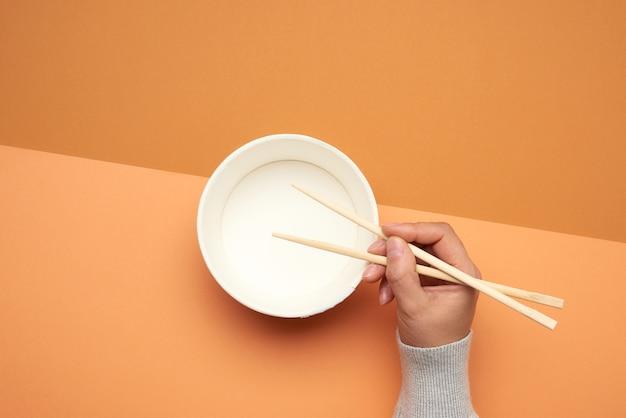 女性の手と空の紙皿に木製の箸のペア