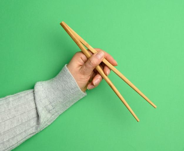 Пара деревянных палочек для еды в женской руке на зеленом фоне, крупным планом