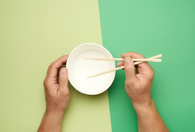 Пара деревянных палочек для еды в мужской руке и пустая бумажная тарелка, вид сверху