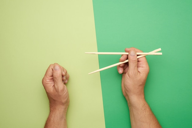 男性の手に木製の箸のペア
