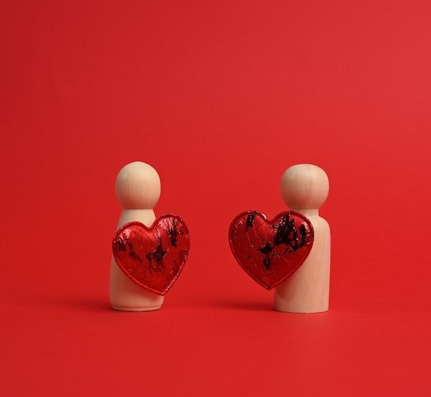 Пара деревянных мужчин жениха и невесты, между ними красное сердце, красный фон, концепция любви и отношений