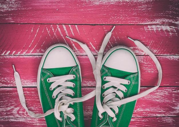 분홍색 녹색 오래 된 나무 표면에 착용 된 운동 화 한 켤레