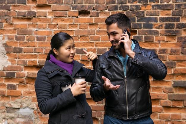 壁を背景にした若者のペア、男は同時に女の子と電話で話している