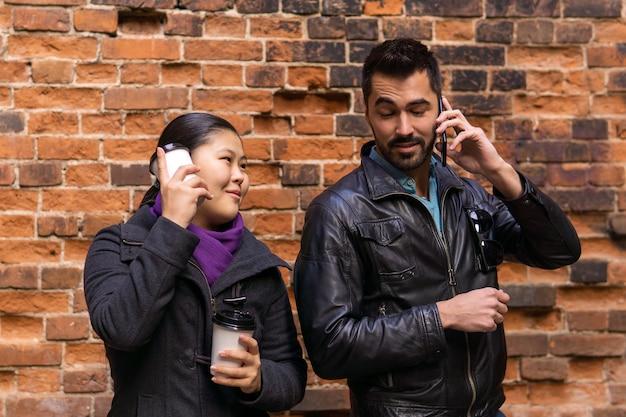 若い人たちのペアは長い間電話で話している女の子はイライラして彼をパロディーにしています