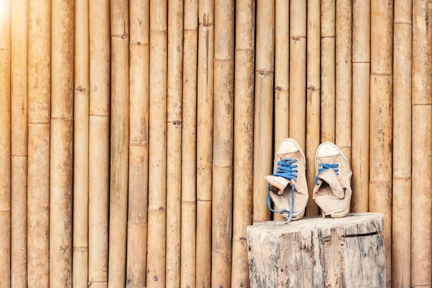 Pair of old classic sneakers leaning against a bamboo wall. travel concept background.