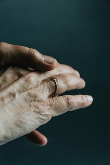 A pair of old hands showing a jewelry ring on the finger over a dark background