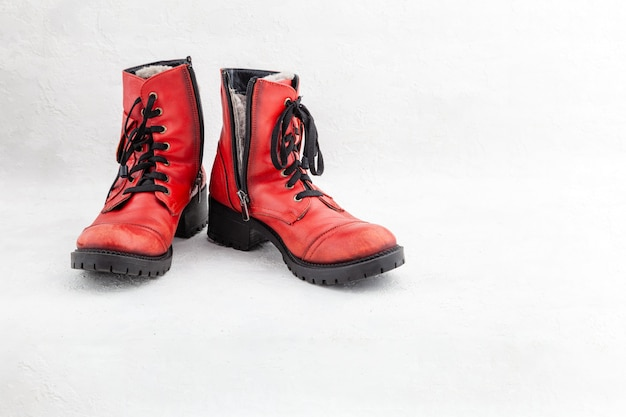Pair of old leather red discarded boots with laces