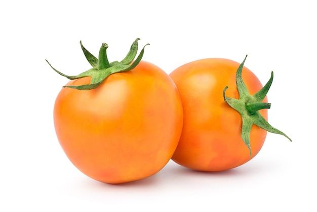 Pair of orange tomatoes isolated on white background.