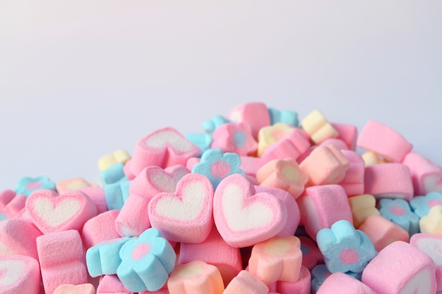 Pair of pink and white heart shaped marshmallow on the pile of flower shaped marshmallow candies