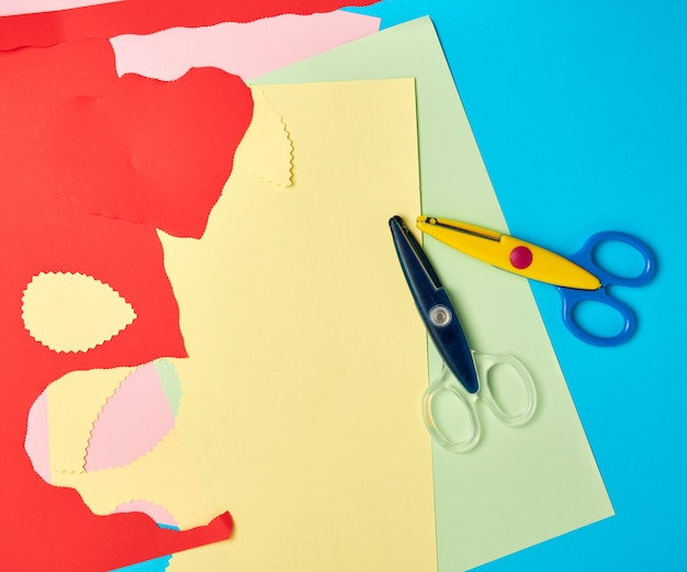 Pair of plastic scissors and colored paper for cutting figures