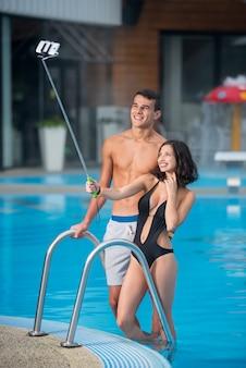Pair posing against swimming pool