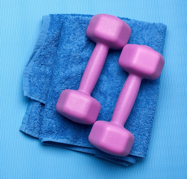 Pair of purple dumbbells and blue towel on a blue