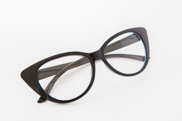 Pair of reading glasses or spectacles with modern dark frames folded up on white