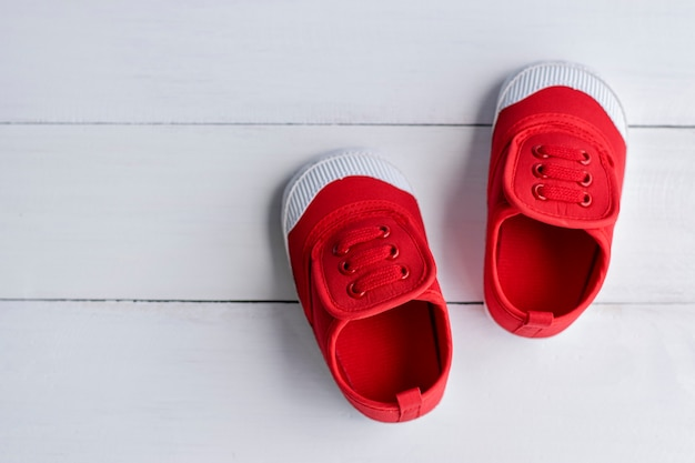 A pair of red baby boy shoes on white wooden floor