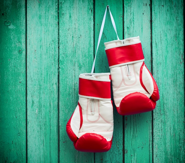 Pair of red boxing gloves hanging on a nail on a surface of green wood surface