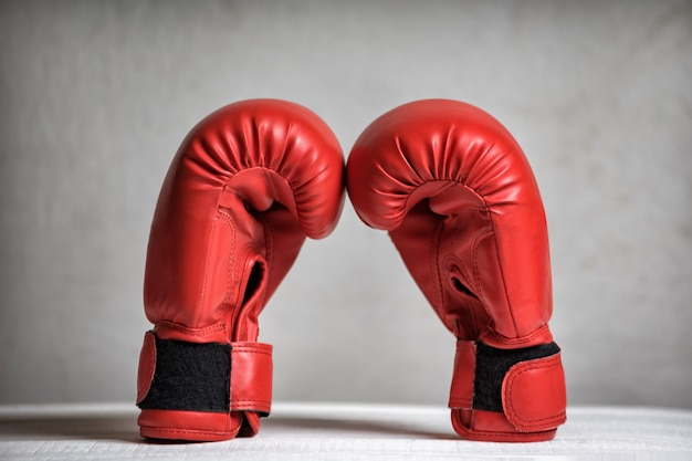 Pair of red boxing gloves on white