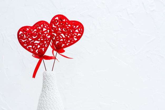 A pair of red curly hearts in a white vase decorated by knitting. copy spase