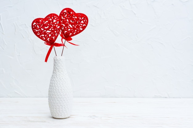 A pair of red curly hearts in a white vase decorated by knitting on the table. copy spase