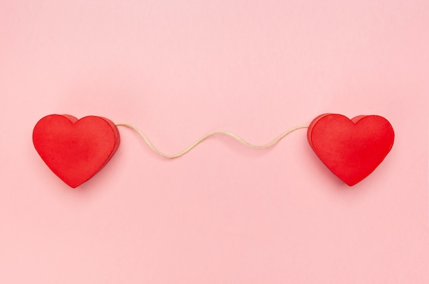 Pair of red hearts connected with a string of twine