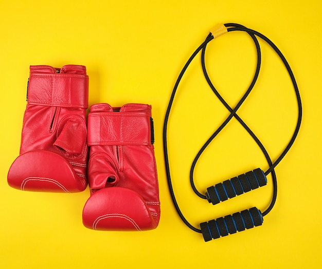 Pair of red leather boxing gloves and black trainer hand expander