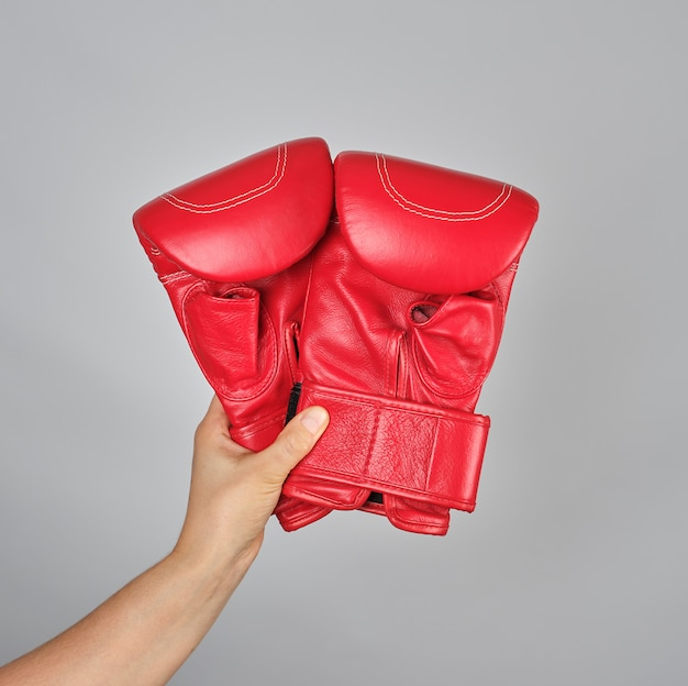 Pair of red leather boxing gloves in female hand