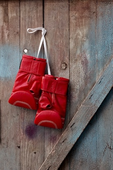 Pair of red leather boxing gloves hanging on a nail
