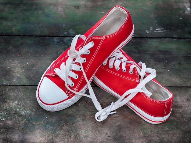 Pair of red sneakers youth on an old wooden surface
