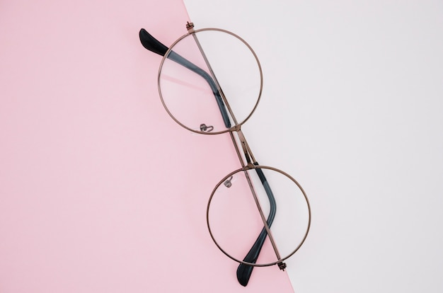 Pair of round glasses on a rose and white background