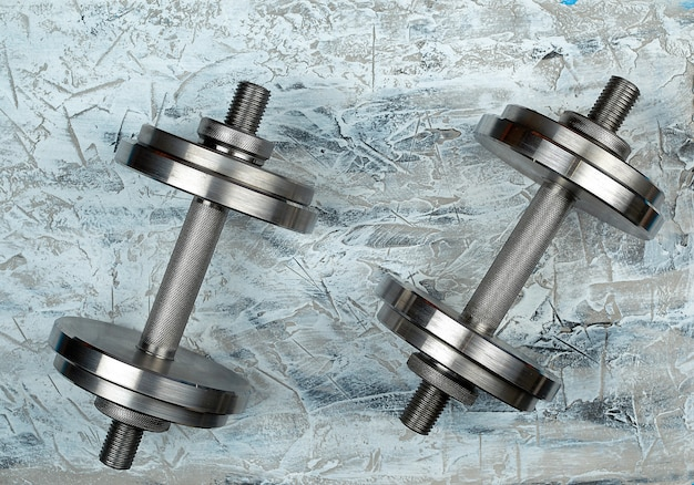 Pair of shiny steel typesetting dumbbells for bodybuilding on a gray