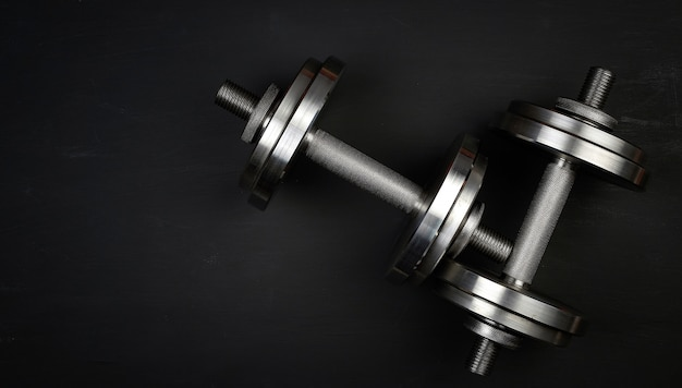 Pair of shiny steel typesetting dumbbells for bodybuilding