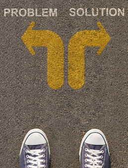 Pair of shoes standing on a road with arrow