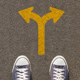 Pair of shoes standing on a road with traffic sign