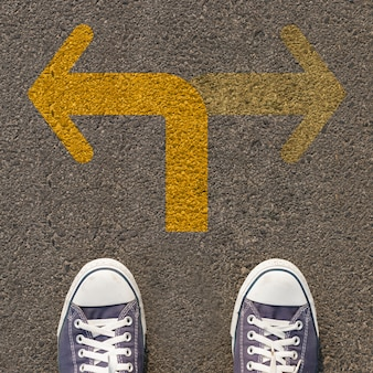 Pair of shoes standing on a road with two way yellow arrow