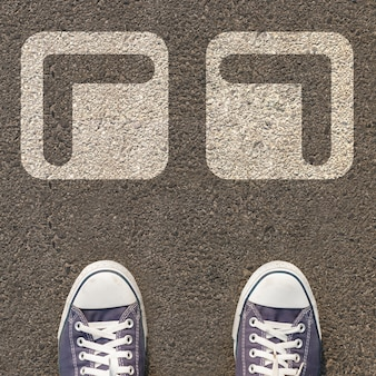 Pair of shoes standing on a road with two white arrow